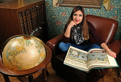 Student with atlas and globe in Special Collections